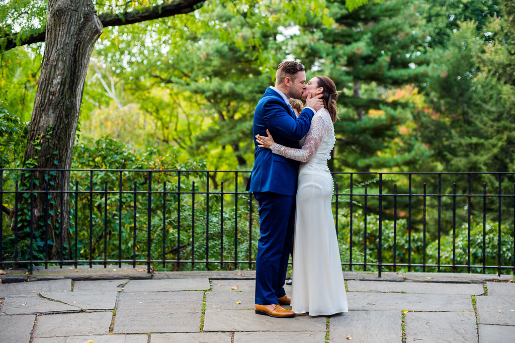 Couple seals their marriage with a kiss on a balcony by the Shakespeare Garden.